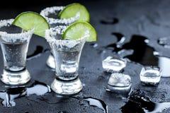 Tiros de prata do tequila com gelo e cal no fundo preto da tabela Fotografia de Stock