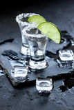Tiros de prata do tequila com gelo e cal no fundo preto da tabela Foto de Stock