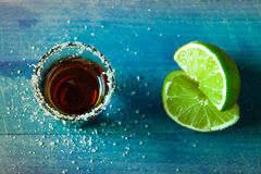 Tiros del alcohol con la cal y la sal en la tabla azul de madera Imagenes de archivo