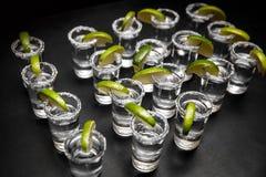 Tiros do Tequila com cal e sal na tabela preta foto de stock