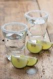 Tiros do Tequila com cal na tabela, foco seletivo Imagem de Stock Royalty Free