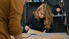 3 tiros Dos decoradores de las mujeres profesionales, diseñadores que hacen sobres almacen de metraje de vídeo