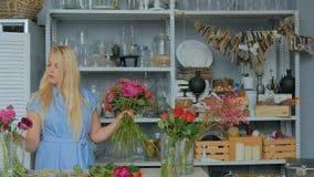 4 tiros Florista profesional que hace la composición floral de la boda en la floristería almacen de video