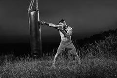 Tiros monocromáticos de un entrenamiento masculino del boxeador con un ou del saco de arena Fotos de archivo