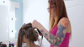 2 tiros Peluquero profesional que hace el peinado para la muchacha bastante adolescente almacen de video