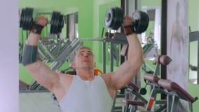 2 tiros Pesas de gimnasia de elevación atléticas del hombre joven en el gimnasio almacen de metraje de vídeo