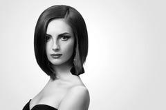 Tiros preto e branco do estúdio de uma jovem mulher elegante com curto Imagens de Stock