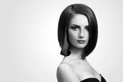 Tiros preto e branco do estúdio de uma jovem mulher elegante com curto Imagens de Stock Royalty Free
