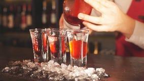 Tiros rojos del cóctel en el vidrio aislado en fondo borroso del restaurante almacen de video