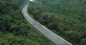 Tiroteo aéreo de la carretera con los coches y las motos en país tropical cerca del bosque salvaje de las palmeras almacen de video