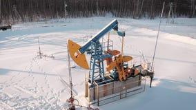 Tiroteo aéreo de una unidad de bombeo del aceite en el medio de un campo, estación del invierno almacen de video