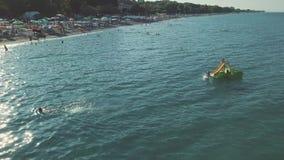 Tiroteo aéreo Mire desde arriba la gente que se baña en el mar almacen de metraje de vídeo