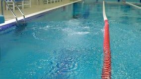 Tiroteo a cámara lenta de un salto del ` s del atleta en la piscina almacen de video