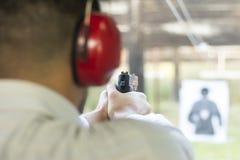 Tiroteo con el arma en la blanco en radio de tiro Tiroteo de la pistola del fuego practicante del hombre Fotografía de archivo