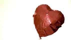 Tiroteo de la flecha a través del globo del corazón en el fondo blanco almacen de metraje de vídeo