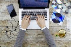 Tiroteo de la mujer joven desde arriba del trabajo en el ordenador portátil en la tabla de madera que escucha el Cd de la música  imagen de archivo libre de regalías