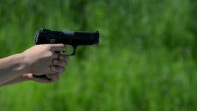 Tiroteo de la pistola en fondo verde almacen de video