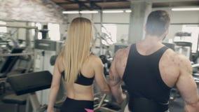 Tiroteo de los pares traseros que caminan entre el entrenamiento en gimnasio del deporte