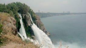 Tiroteo de Timelapse de una cascada tempestuosa, pequeñas ondas en el mar y una vista de la ciudad en la distancia metrajes