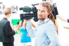 Tiroteo del cameraman con la cámara en sistema de la película Foto de archivo