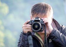 Tiroteo del hombre con una cámara de Nikon DSLR foto de archivo libre de regalías