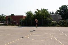 Tiroteo del jugador de básquet en un patio Fotografía de archivo