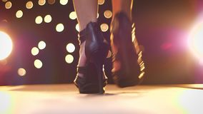 Tiroteo del primer del calzado en luces, tacón alto de la hembra, caminando de cámara en fondo que brilla intensamente dentro metrajes