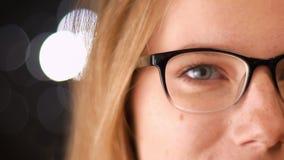 Tiroteo del primer de la mitad-cara bonita en gafas de la mujer caucásica rubia que se coloca relajada y que mira la cámara metrajes