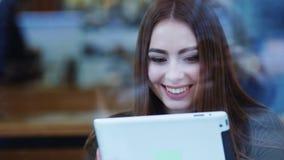 Tiroteo exterior de una mujer joven hermosa en una mirada elegante que se sienta por la ventana en un café y que practica surf I almacen de video