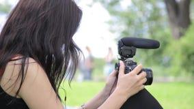 Tiroteo femenino del director de cine del indie de la raza mixta joven en un ajuste natural verde con la hierba en fondo metrajes