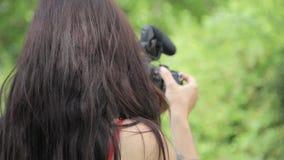 Tiroteo femenino del director de cine del indie de la raza mixta joven en un ajuste natural verde con la hierba en fondo almacen de video