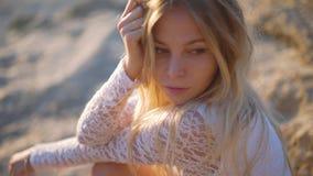 Tiroteo hermoso del primer de la muchacha mira el mar y la cámara shooted sobre hora de oro cara emocional en la playa metrajes
