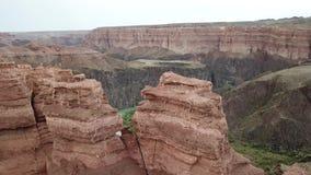 Tiroteo liso con el abejón Vista del barranco y del río de Charyn El río de la turquesa atraviesa el barranco rocoso rojo almacen de video