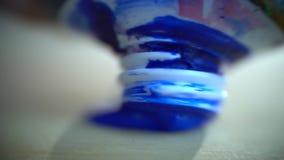 Tiroteo macro como pintura azul de los apretones blancos del tulipán y manchado lentamente en una paleta de madera almacen de video