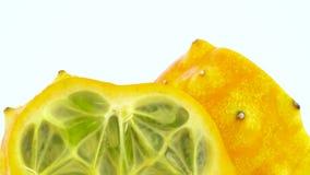 Tiroteo macro Parte superior de dos mitades de la fruta madura del kiwano Lentamente girando en la placa giratoria aislada en el  metrajes