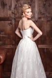 Tiroteo nupcial de la belleza de la moda Novia hermosa de la moda en el vestido de boda que presenta delante de fondo arbolado Imagen de archivo libre de regalías