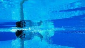 Tiroteo subacuático como nadadas de un hombre debajo del agua en la piscina C?mara lenta almacen de video