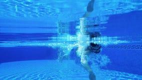 Tiroteo subacuático como nadadas de un hombre debajo del agua en la piscina almacen de metraje de vídeo