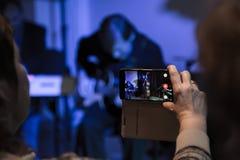 Tiroteo video con su smartphone Película del concierto Músicos que tocan el bajo doble y la guitarra eléctrica Imagenes de archivo