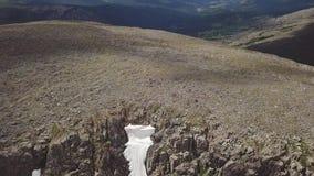 Tiroteo video del aire que sube encima de la montaña con muchas piedras y de un glaciar de la nieve en el verano en las montañas