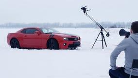 Tiroteos comerciales, charla del director en el altavoz, coche rojo del músculo en campo de nieve metrajes