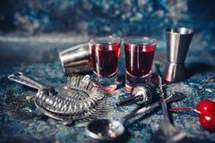 Tirs de cocktail de boisson Tirs forts et rouges de vodka avec la cerise et saveurs de delicios photo libre de droits