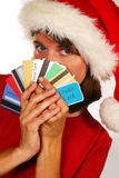 Tis the Season. Adult woman in santa hat hiding behind credit cards (holiday spending and debt Stock Photography