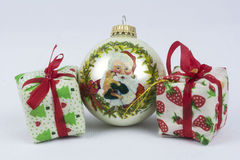 Tis the season. Two Christmas gifts with a Christmas bulb on a white back ground Stock Photo