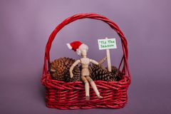 Tis the Season picket sign held by jointed manikin doll wearing Santa hat red basket and pine cones Christmas scene. Tis the Season white picket sign held by stock photos