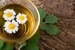 Tisana con la camomilla sulla vecchia tavola di legno Vista superiore Concetto della medicina alternativa Immagini Stock