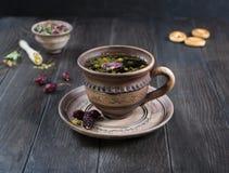 Tisana, erbe e fiori in una tazza dell'argilla con il biscotto sulla tavola di legno Fotografia Stock