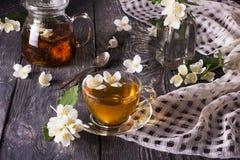 A tisana no bule e no copo, flores do jasmim dispersou na tabela de madeira foto de stock