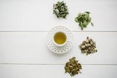 Tisana perfumada e saudável fresca em um vidro ou em uma caneca em uma superfície de madeira branca Ao lado dele várias ervas sec Imagem de Stock Royalty Free