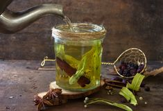 Tisane chaude délicieuse : tilleul, rose de chien, menthe, cannelle Thé chaud étant renversé dans un verre photographie stock
